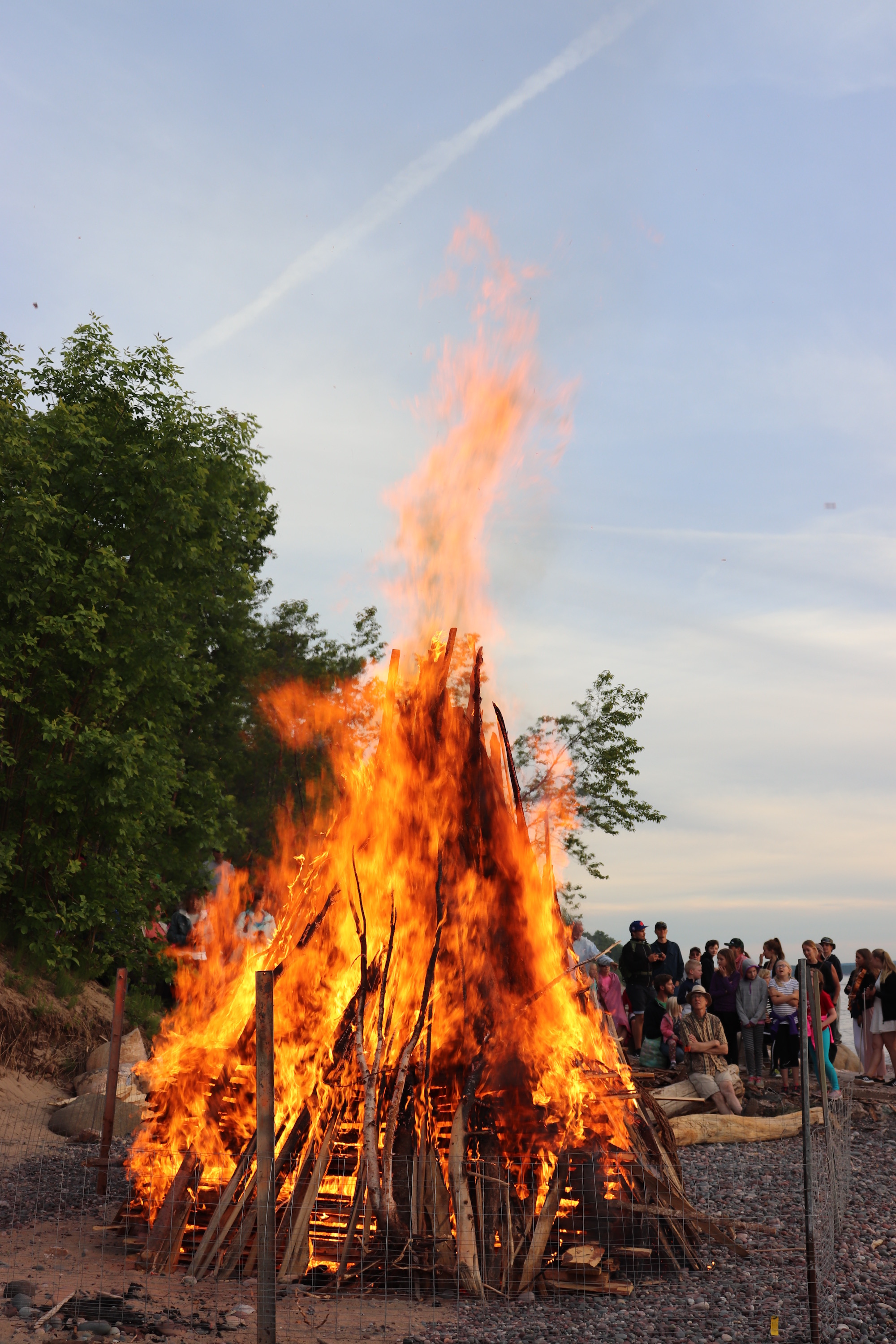 The bonfire is lit and reaches towards the evening sky.