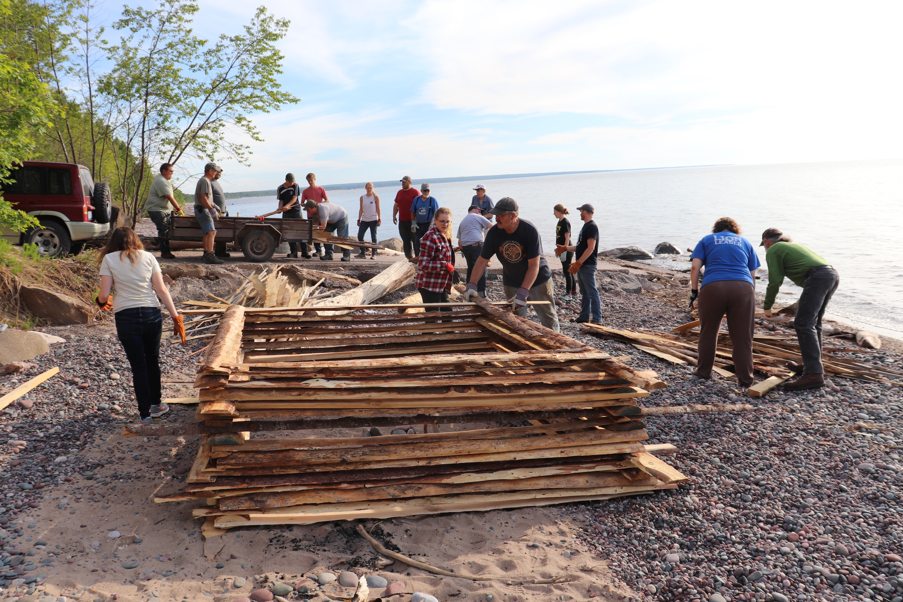 Volunteers begin to build the protective base of a bonfire