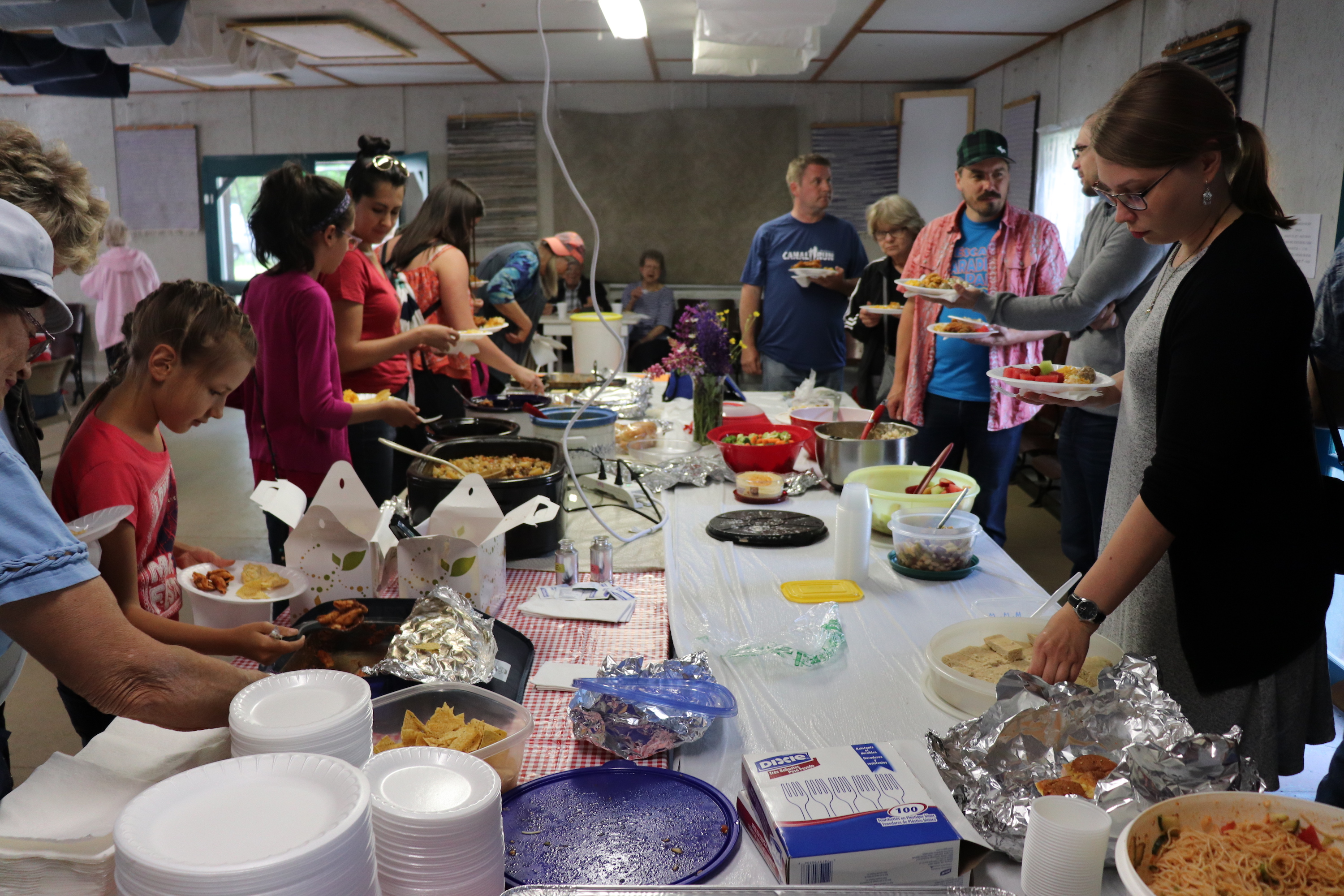 People fill their plates with food from the potluck before the bonfire.