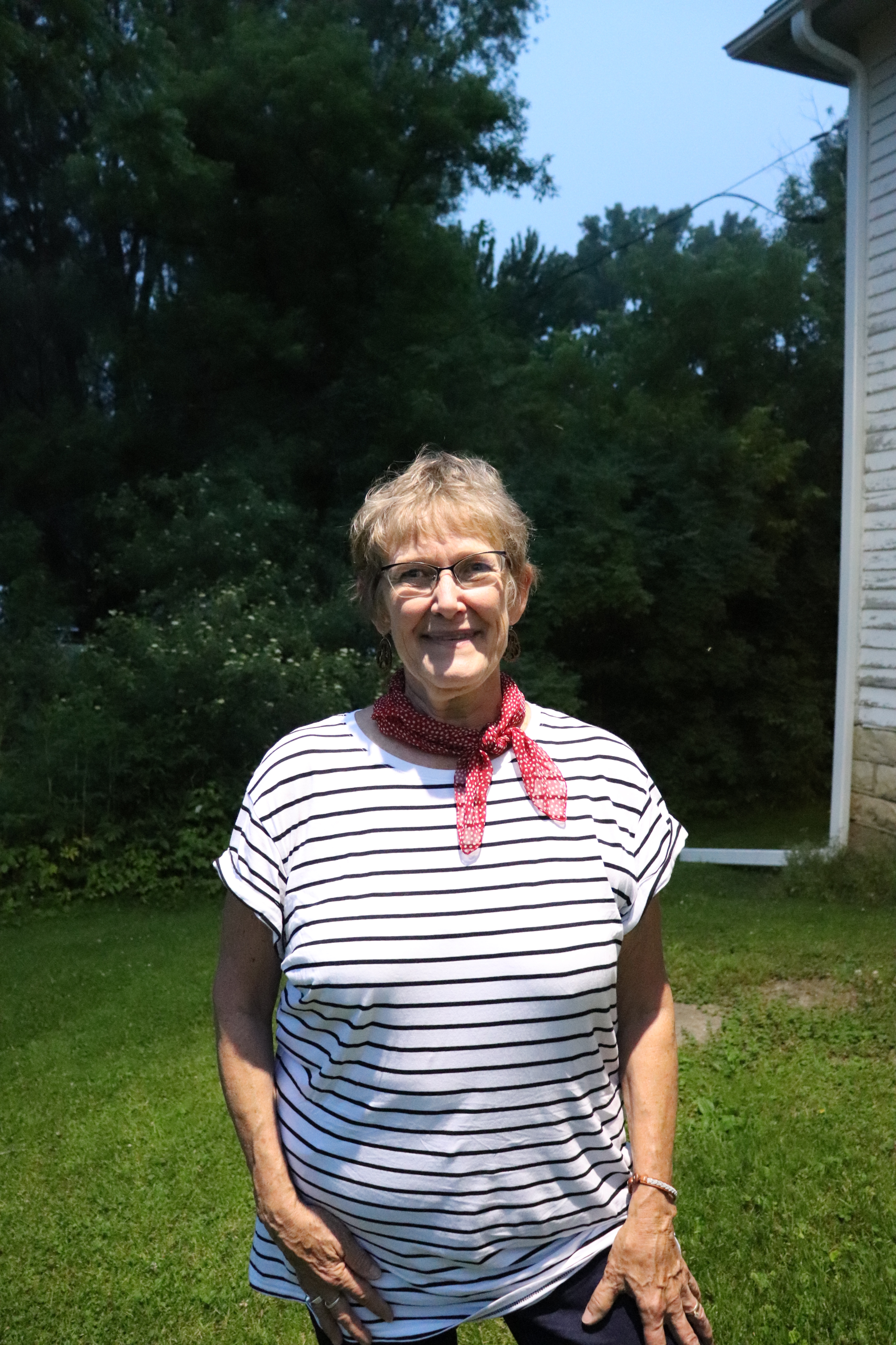 Carol Bergan stands outside the schoolhouse.