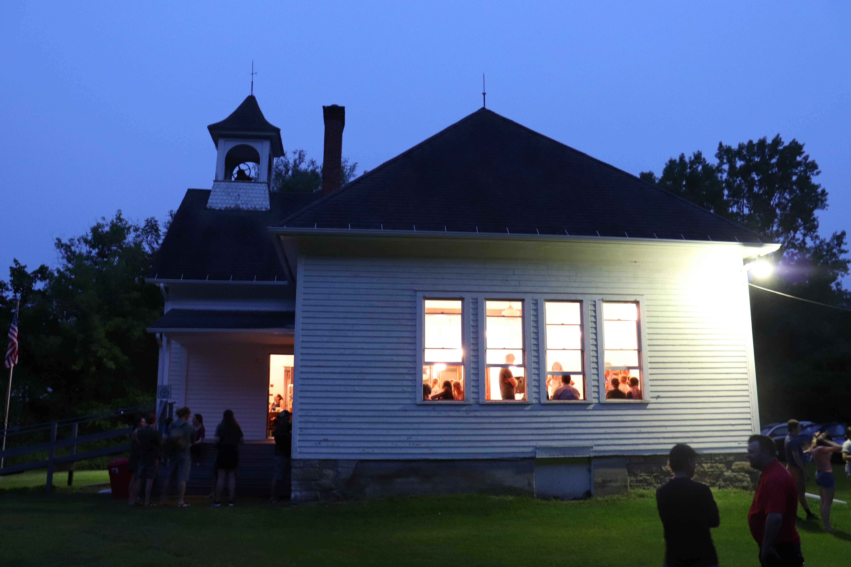 The Highlandville School House lit up under the night sky.