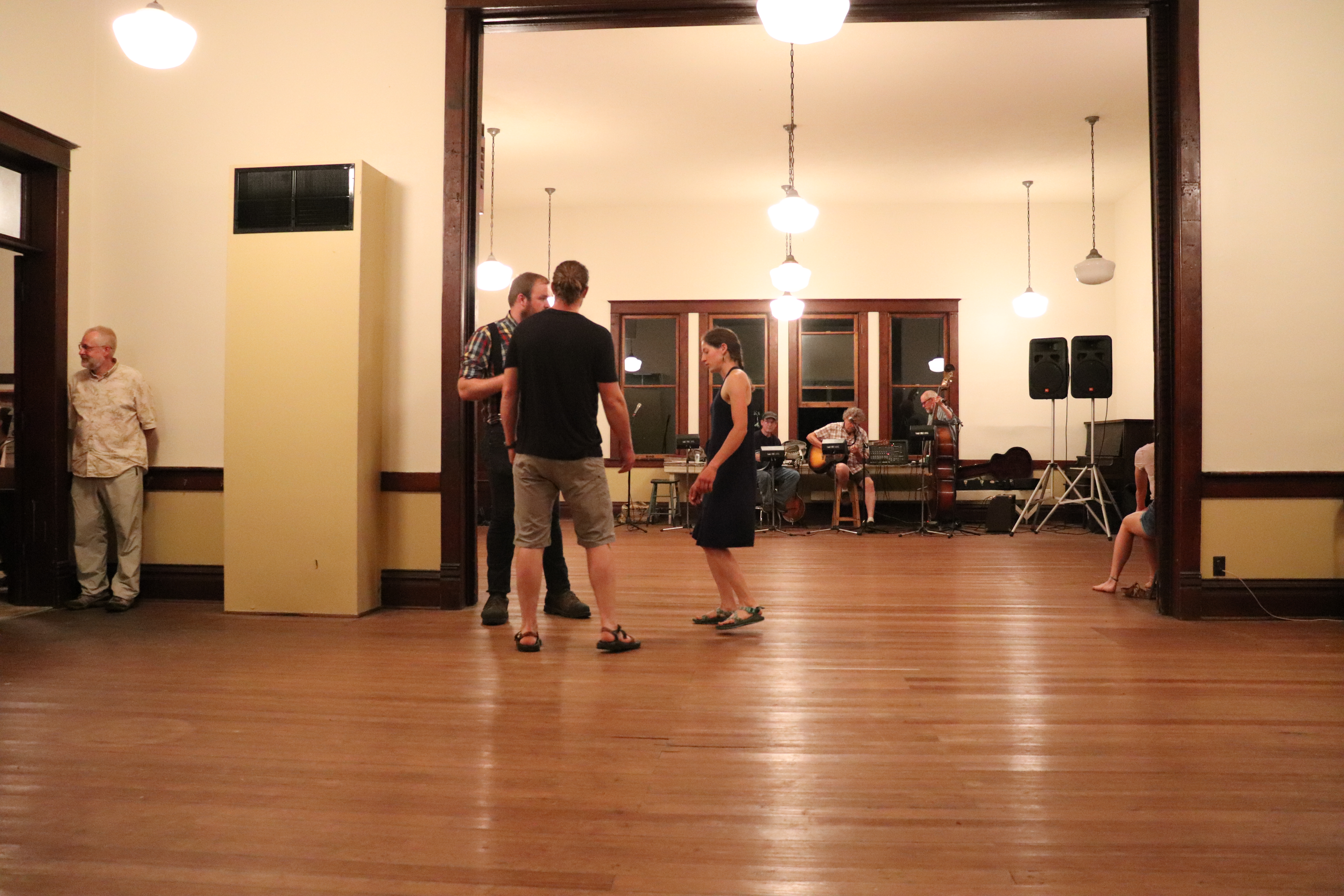 A couple teaches a young man to dance during a break in music.