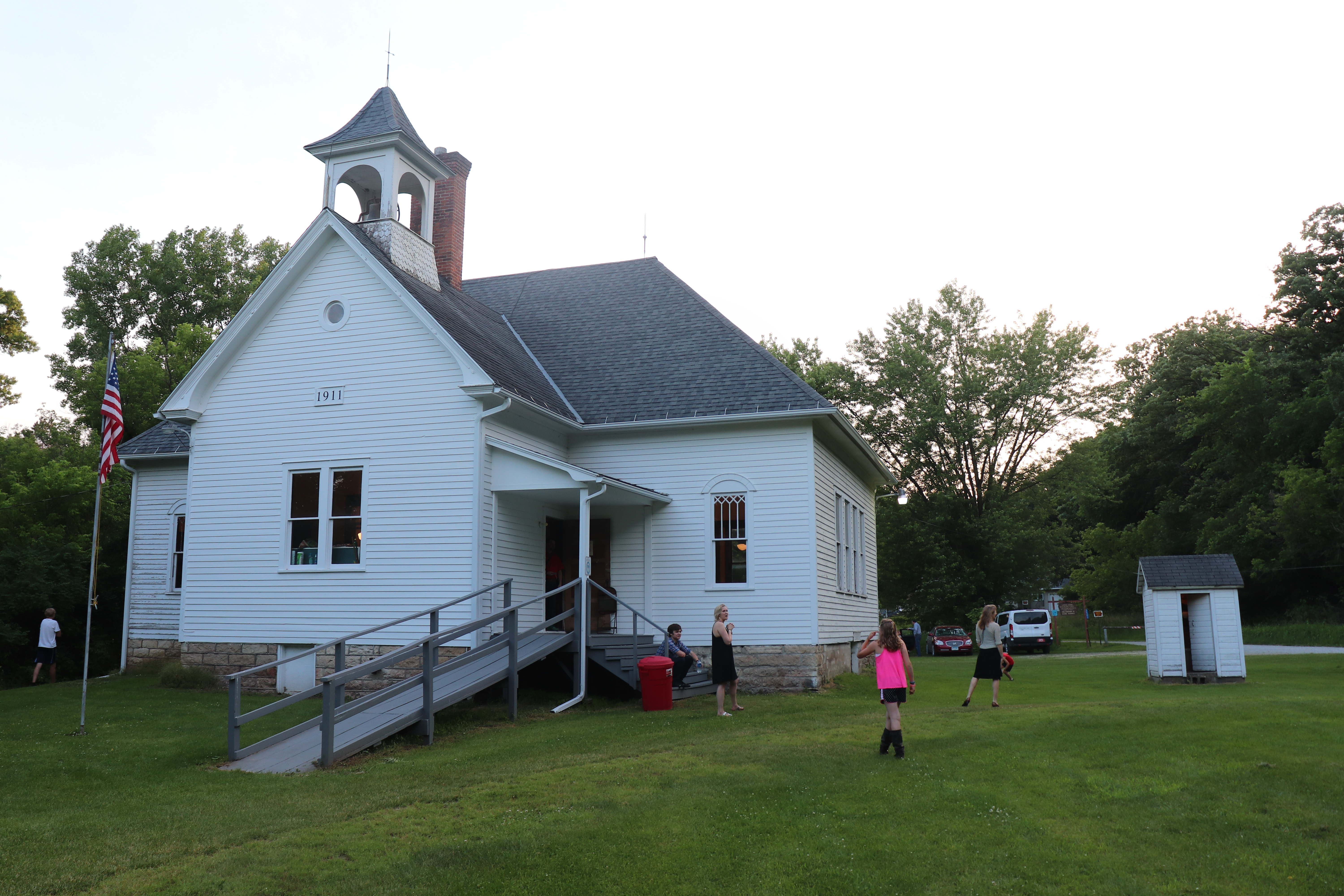 People standing outside of the Highlandville School House