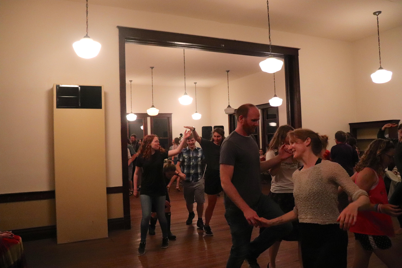 A group of people dance the schottische.