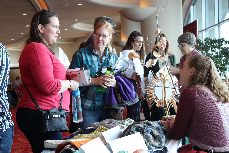 Auður Björt Skúladóttir speaks with attendees about her knitting.
