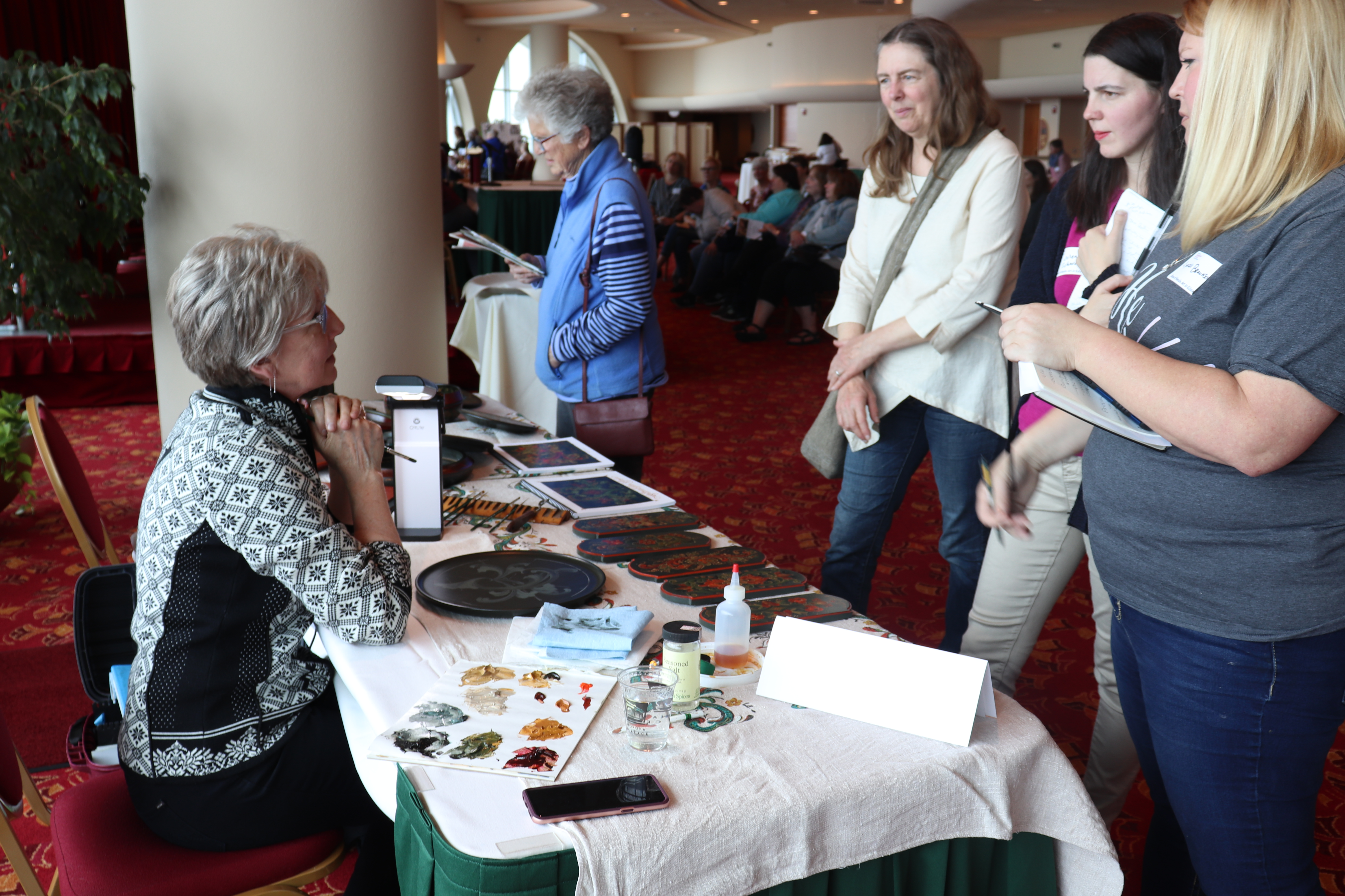Andrea Herkert shows audience members her rosemaling.