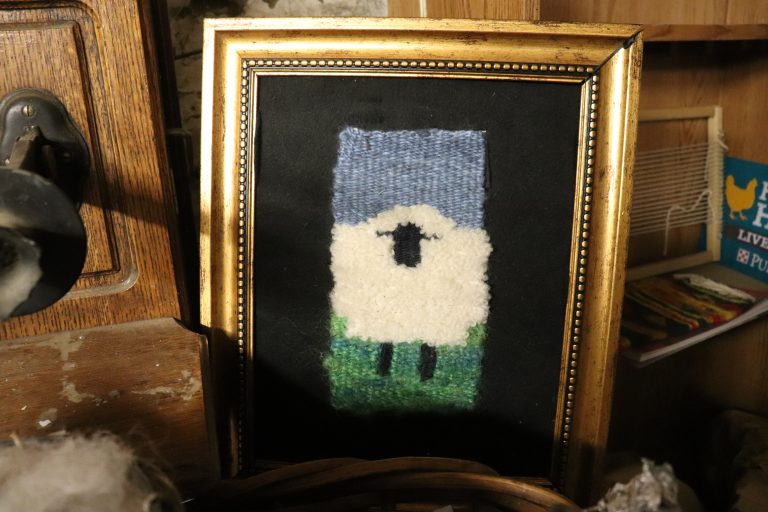 A framed weaving of a sheep