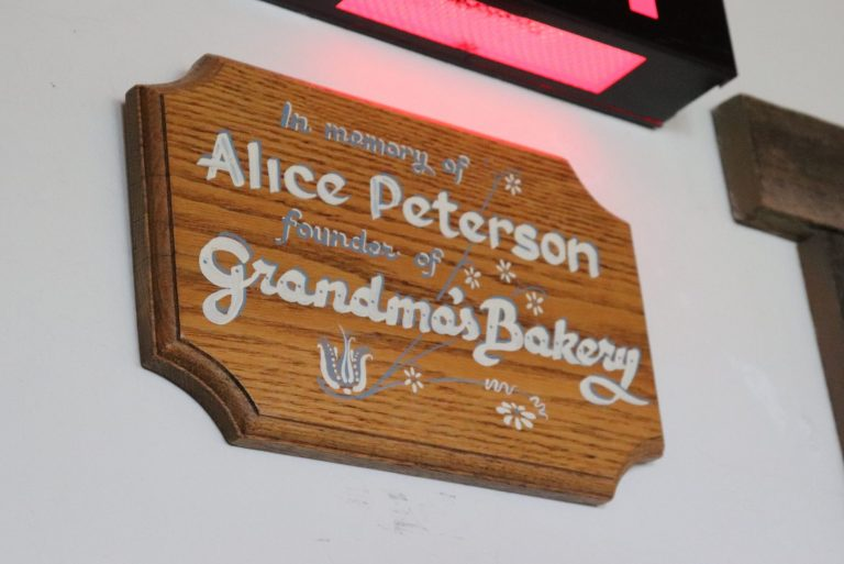 """Wall plaque reads """"In memory of Alice Peterson, founder of Grandma's bakery"""""""