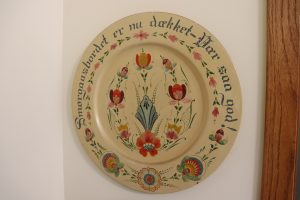 A yellow wooden platewith rosemaling in blue, red, and green and text in Norwegian around the edge.