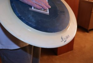 Ann Walser shows the back of a plate with the name Lysne visible on the bottom edge.