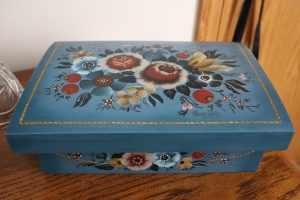 A blue jewelry box painted with flowers in the Valdres style in white, red, yellow, and green.