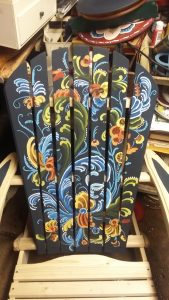 An adirondack chair with the back rosemaled in black, red, blue, and yellow.