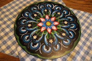 A rosemaled plate lies on top of a checkered tablecloth. The plate is painted in back, blue, red, white, and green.