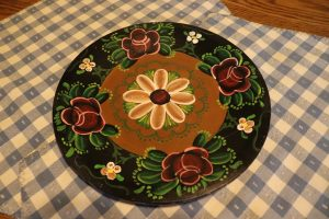 A wooden plate rosemaled in purple, black, green, and white. The plate is laying on a table on top of a blue and white checkered tablecloth.