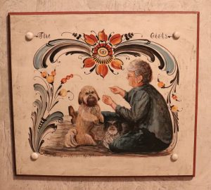 A painted image with rosemaling on the top, an older woman sitting on the ground on the right, and a small dog on the left.