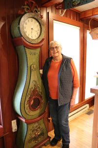 Karen Jenson, an older woman wearing an orange shirt and blue vest stands next to a grandfather clock that she rosemaled.