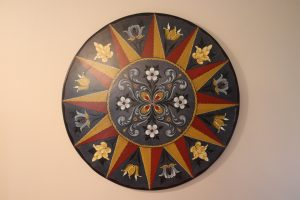 A large wooden plate with a Hallingdal design painted on top in red, yellow, and blue, rests on a white wall.