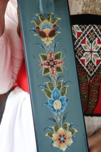 A blue mangle board with four rosemaled flowers in red, blue, yellow, and green.