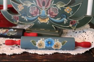 A miniature rolling pin in blue with blue and white rosemaled flowers rests on top of a white crocheted doily. A green rosemaled candleholder stands behind it.