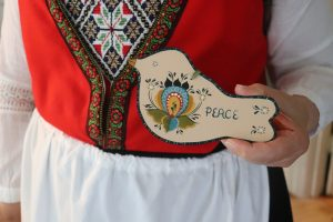 Koehler, wearing a bunad, holds a wooden dove ornament painted with a rosemaled decoration and the word peace.