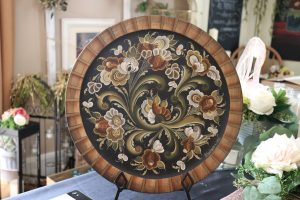 A wooden plate rosemaled in a Telerogaland pattern in black, tan, red, and white.