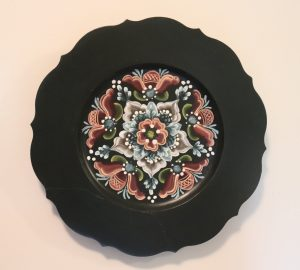 A black plate with decorative edging and a Rogaland design painted in red, blue, and white.