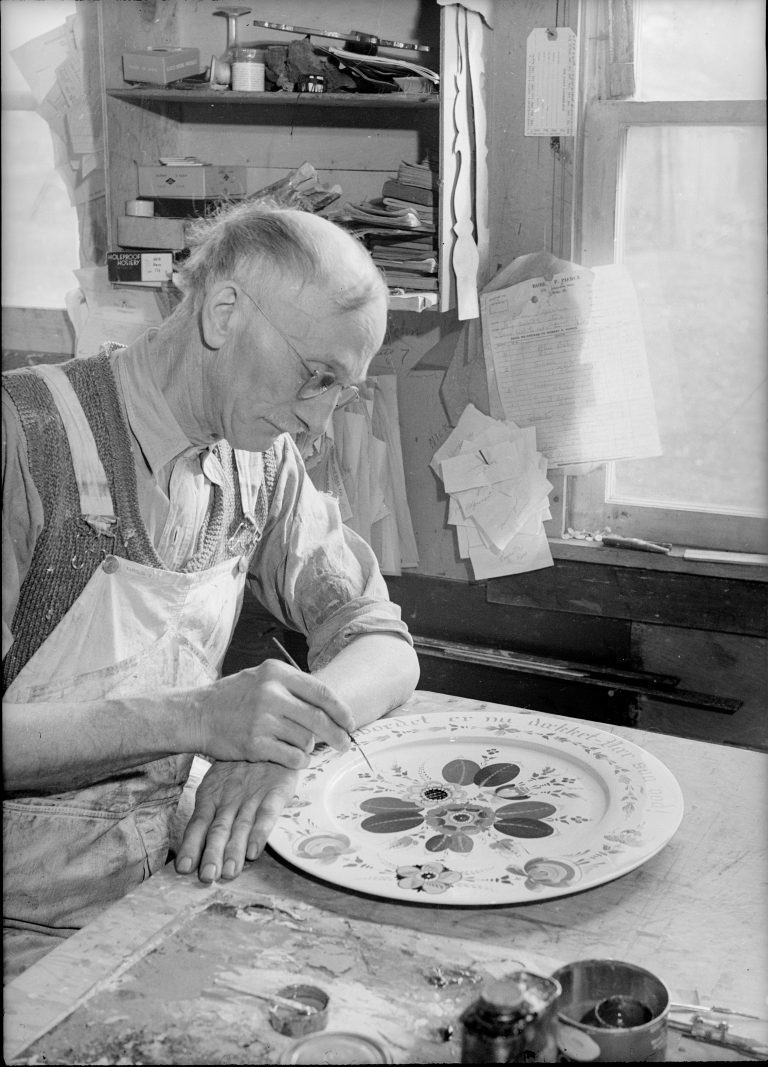 A black and white photo of Lysne holding a paintbrush and rosemaling a plate at a table in his studio.