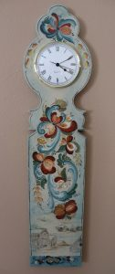 A light blue wall clock with a wooden base painted in the Telemark style in red, blue, and yellow. Below the Telemark design is a small mountain scene with log cabins at the bottom.