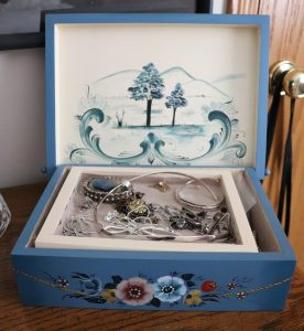 The inside of a jewelry box shows jewelry in a tray and the inside lid has a chinoiserie mountain and tree scene and scrollwork.