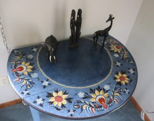 A blue table Magnusson painted in blue with a Hallingdal design in yellow and red. A small figurine of an elephant, giraffe, and a third sit on top of the table.