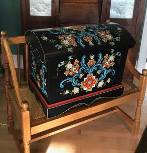 A black trunk with rosemaling design in blue, red, and yellow sits on top of a wooden bench.