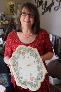 Haukoos, a woman with brown hair and a red and orange patterned shirt, holds a wall clock she painted with a rosemaled design around the edge.