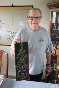 Ed Rosencrantz, an older man wearing a grey t-shirt, holds up a flat piece of wood that he rosemaled, painted in black, red, white, and blue.